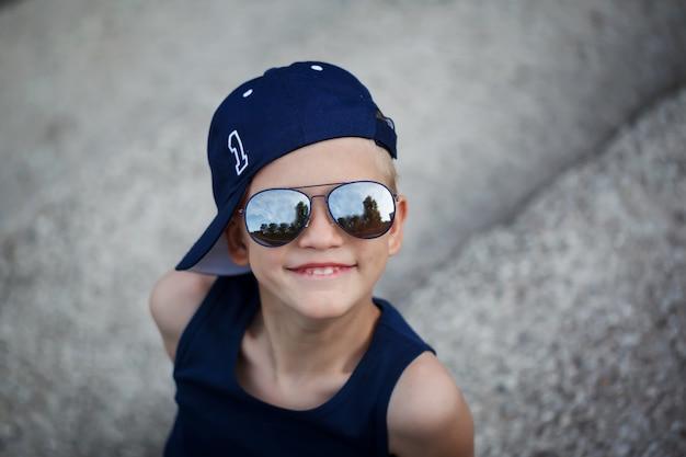 Portret van modieuze kleine jongen in zonnebril en cap. childhood. summertime.