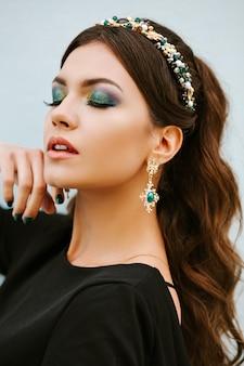 Portret van modieuze meisjesbrunette met een schitterende heldere make-up. de ogen zijn gesloten. stijlvolle dure sieraden, een hoofdband, een hoepel met edelstenen, diamanten oorbellen.