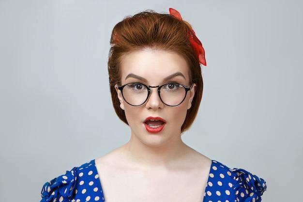Portret van modieuze prachtige jonge blanke dame met perfecte huid en lichte make-up close-up in stijlvolle glazen mond openen in shock, vol ongeloof uiten