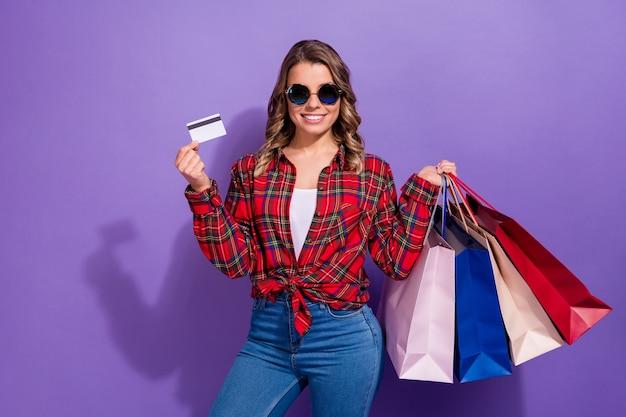 Portret van modieuze, vrolijke, betrouwbare meid met boodschappentassen voor bankkaarten