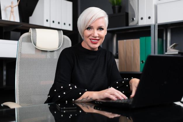 Portret van modieuze vrouw die met laptop in bureau werkt