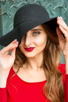 Portret van modieuze vrouw in rode jurk met zwarte hoed