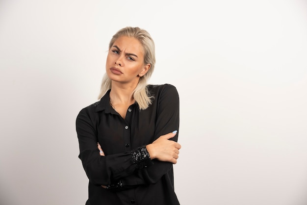 Portret van modieuze vrouw in zwarte shirt poseren op witte achtergrond. hoge kwaliteit foto