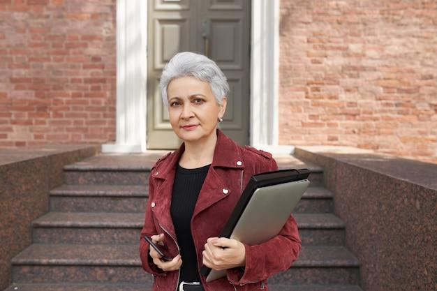 Portret van modieuze zakenvrouw van middelbare leeftijd met kort kapsel staande op de drempel met mobiele telefoon en elektronische gadgets in haar handen