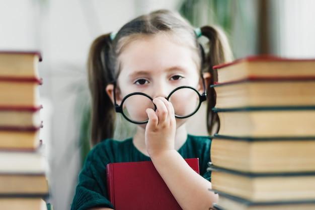 Portret van moe van het lezen van meisje met grote ronde bril op haar neus tussen boeken