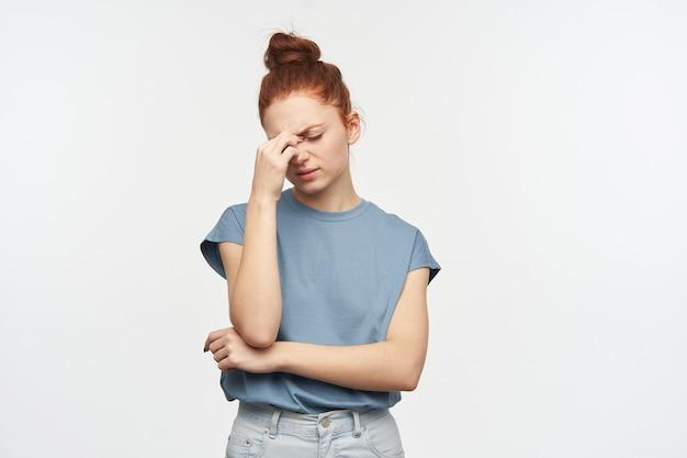 Portret van moe, volwassen roodharig meisje met haar verzameld in een knot. blauw t-shirt en spijkerbroek dragen. aanrakende neusbrug, hoofdpijn. tribune geïsoleerd over witte muur