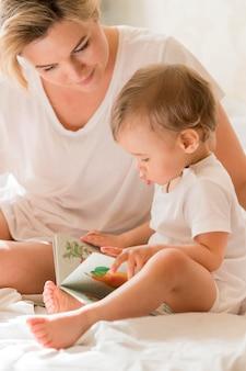 Portret van moeder die aan baby in bed leest