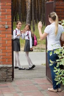Portret van moeder die afscheid neemt van haar dochters die naar school gaan