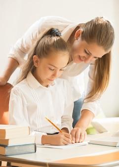 Portret van moeder die dochter helpt bij het voorbereiden op examen