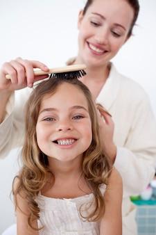 Portret van moeder die het haar van haar dochter doet