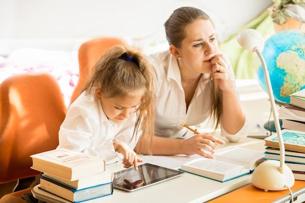 Portret van moeder die naast dochter zit en huiswerk maakt