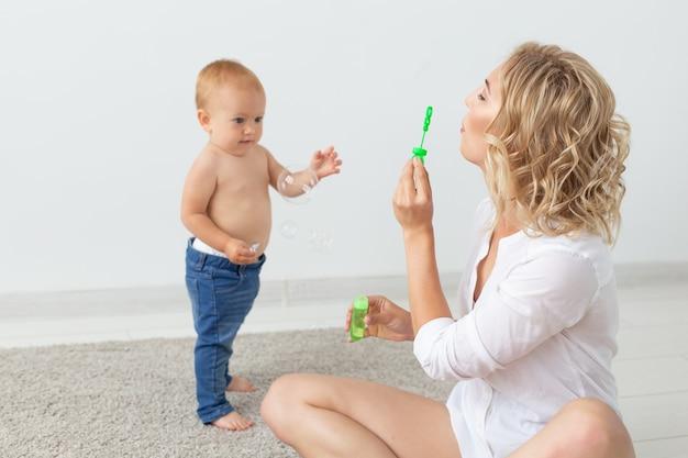 Portret van moeder en baby die en thuis spelen glimlachen