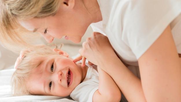 Portret van moeder en baby die zich in bed nestelen