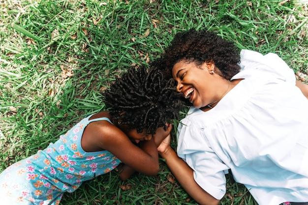Portret van moeder en dochter die gelukkig en glimlachend op het gras liggen