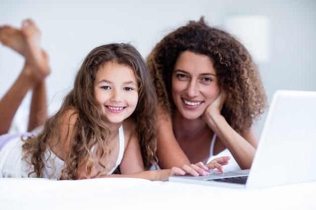 Portret van moeder en dochter die laptop op bed met behulp van