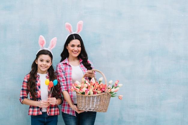 Portret van moeder en dochter die mand van tulpen en paaseieren houden tegen blauwe achtergrond