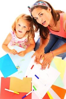 Portret van moeder en dochter die samen over witte achtergrond tekenen drawing