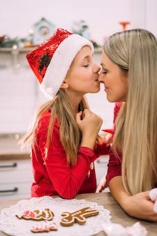 Portret van moeder en dochter. een tienermeisje kust haar moeder in de neus in de keuken met peperkoek