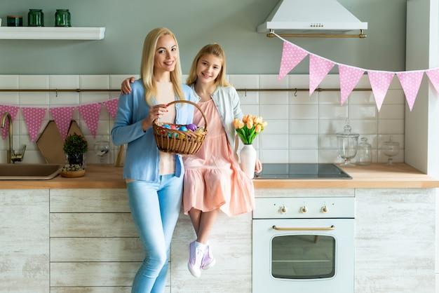 Portret van moeder en dochter in de keuken. ze houden een mand met paaseieren en een boeket tulpen