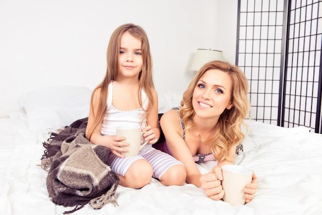 Portret van moeder en dochter liggend in bed met kopjes warme melk