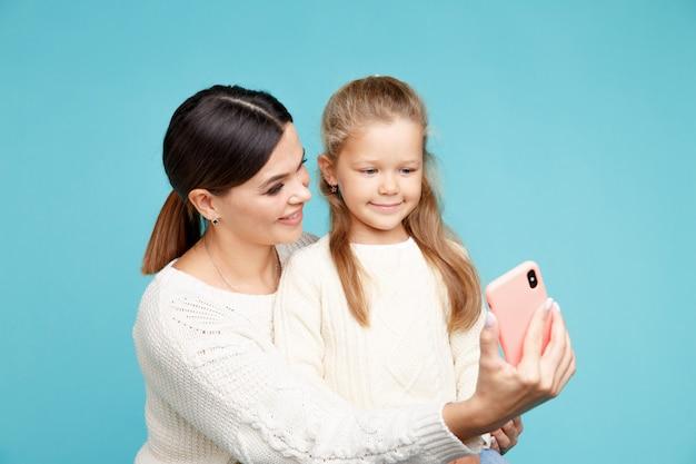 Portret van moeder en dochter met telefoonzitting samen geïsoleerd op blauwe ruimte.