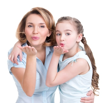 Portret van moeder en dochter sturen kussen - studio-opname op wit