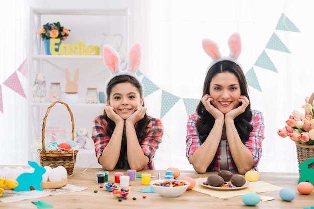 Portret van moeder en haar dochter die paashaasoren dragen die op lijst met pasen-chocolade leunen