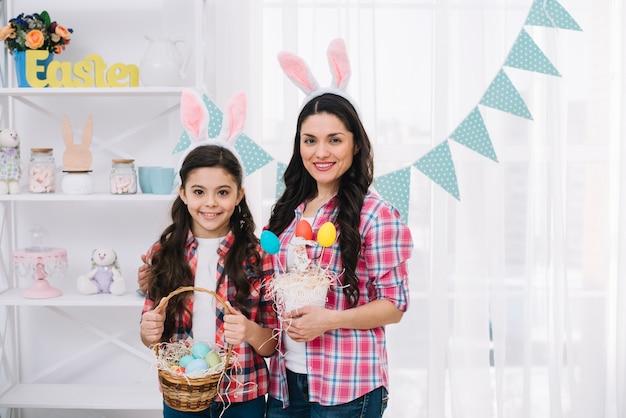 Portret van moeder en haar dochter met konijntjesoren die kleurrijke paaseieren in hand houden