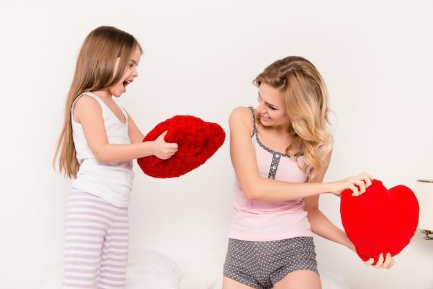 Portret van moeder en haar dochtertje met kussen strijd