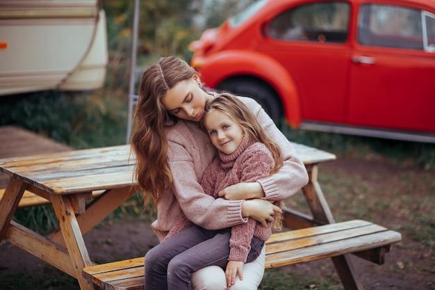 Portret van moeder en kleine dochter knuffelen en ontspannen in het platteland op camper van vakantie met rode retro auto