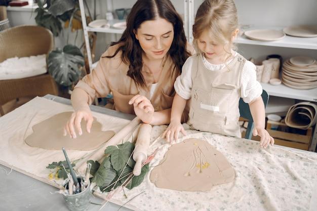 Portret van moeder en meisje die klei samen vormen