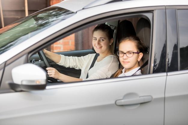 Portret van moeder en twee dochters die in de auto rijden