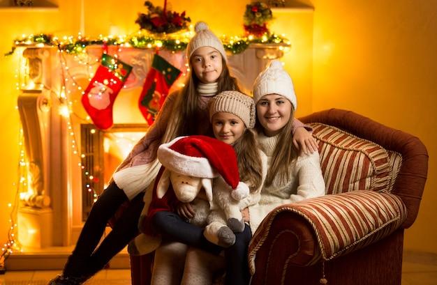 Portret van moeder en twee dochters die op kerstavond op de bank bij de open haard zitten