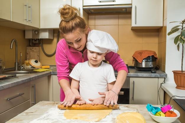 Portret van moeder en zoon die het deeg in de keuken uitrollen. thuis koken