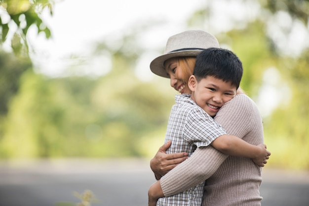 Portret van moeder en zoon gelukkig knuffel samen in het park. familie concept.