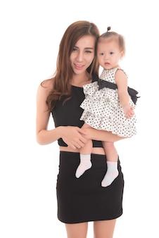 Portret van moeder houdt haar dochter in de armen en kijkt naar camera op witte achtergrond.
