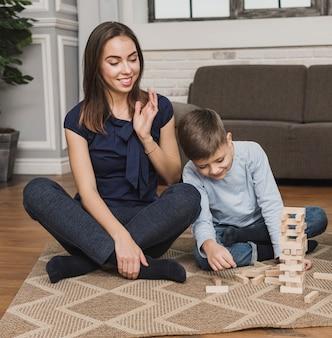 Portret van moeder kijken zoon spelen