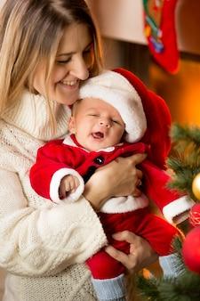Portret van moeder poseren met schattige baby santa