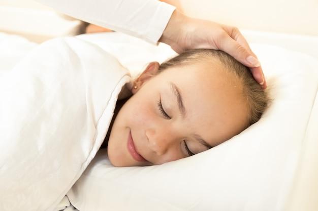 Portret van moederhand die slapende dochter bij de hand streelt