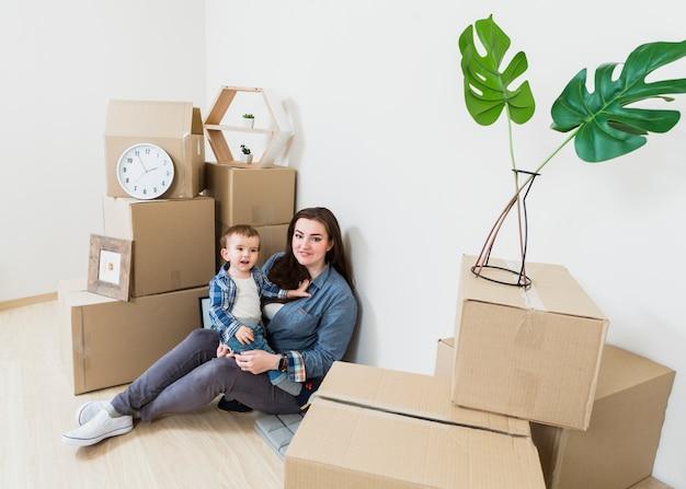 Portret van moederzitting met haar babyjongen onder de kartondozen in nieuw huis