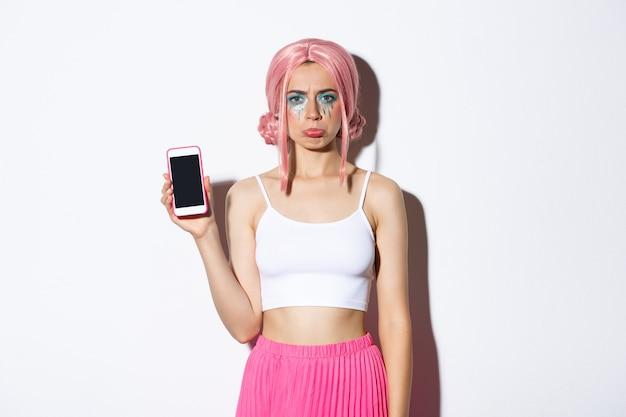 Portret van mokkend meisje dat klaagt en iets teleurstellend toont op het scherm van de mobiele telefoon, staande in roze haar en feestkleding.