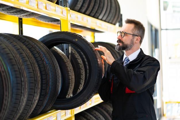 Portret van monteur man met autobanden bij tankstation. mannelijke monteur auto band in auto winkel winkel te houden