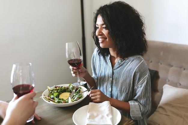 Portret van mooi african american meisje met glas rode wijn in de hand en salade op tafel in restaurant