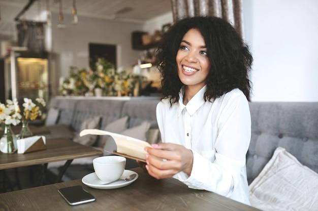 Portret van mooi afrikaans amerikaans meisje in restaurant. jonge lachende dame met donker krullend haar zittend in restaurant met menu in handen