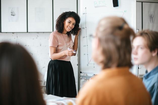 Portret van mooi afrikaans amerikaans meisje met donker krullend haar dat zich dichtbij raad bevindt en presentatie geeft aan collega's in bureau