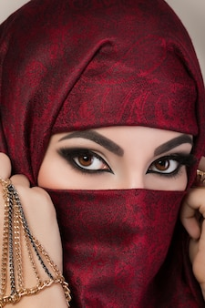 Portret van mooi arabisch meisje dat haar gezicht achter rode niqab met paisley ornament verbergt