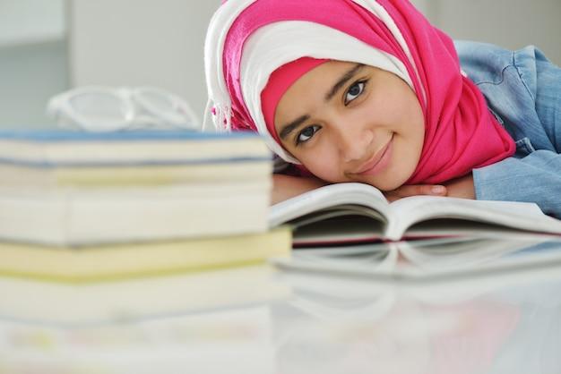 Portret van mooi arabisch moslimmeisje met boeken