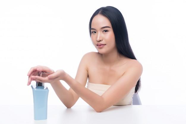Portret van mooi aziatisch meisje dat desinfecterend middel gebruikt