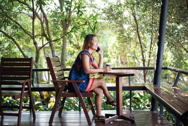 Portret van mooi aziatisch meisje dat haar mobiele telefoon in koffie met behulp van.
