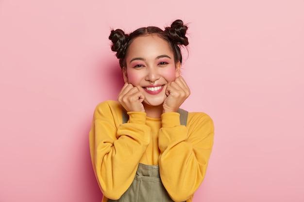 Portret van mooi aziatisch meisje met pinup make-up, houdt kin met beide handen, gekleed in casual outfit, heeft donker haar gekamd in twee broodjes